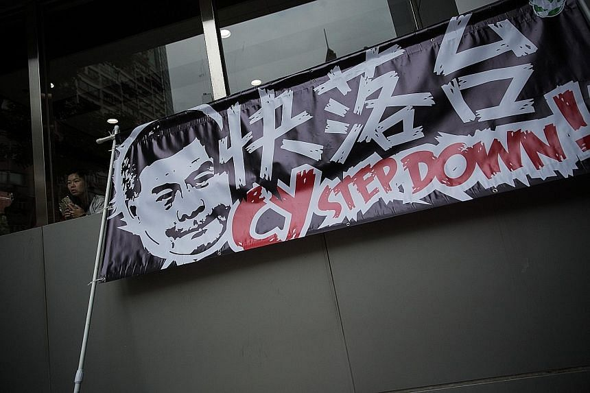 A protest banner on May 18 calling for Mr Leung to step down. Hong Kong is mired in governance paralysis due to a toxic relationship between the government and legislators.