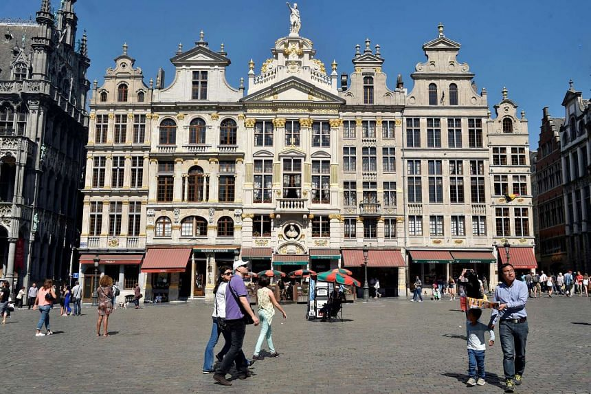 Tourists walk at the Grand Place during a hot and sunny day in Brussels, Belgium.