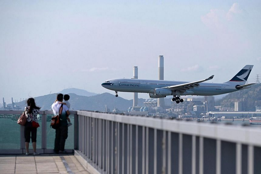 People watch as a Cathay Pacific plane prepares to land at Hong Kong's international airport in August 2014.