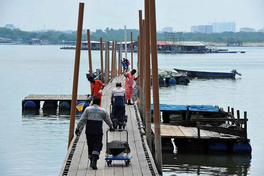 Workers pushing trolleys of dead fish along Lim Chu Kang jetty on July 18.