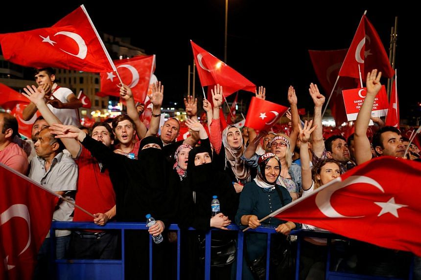 Supporters of Turkish President Tayyip Erdogan shout slogans and wave Turkish national flags during a pro-government demonstration on Taksim square in Istanbul, Turkey, July 18.