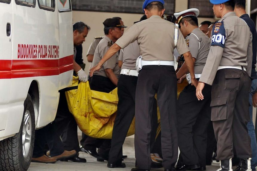 Indonesian police officers carrying body bags containing the body of two members of the East Indonesia Mujahidin (MIT) at a police hospital in Palu, Central Sulawesi, on July 19, 2016.