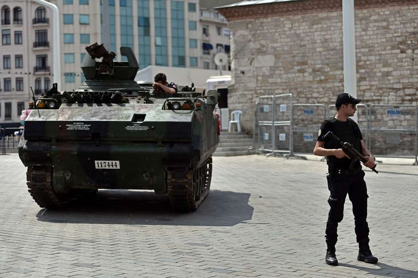 A police officer stands next to an armoured vehicle that was used by soldiers during the coup attempt, in Taksim square in Istanbul, on July 17, 2016.
