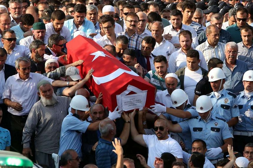 Relatives of the victims who were killed in the coup attempt on July 16, watch as a coffin is carried during a funeral in Ankara, on July 18, 2016.