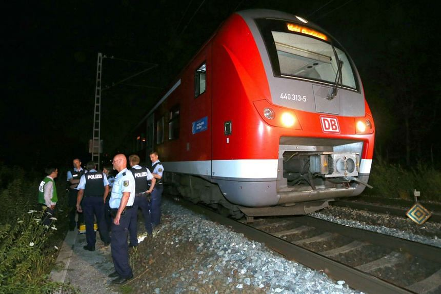 Police officers stand by a regional train in Wuerzburg, southern Germany, on July 18, 2016, after a man attacked train passengers with an axe.