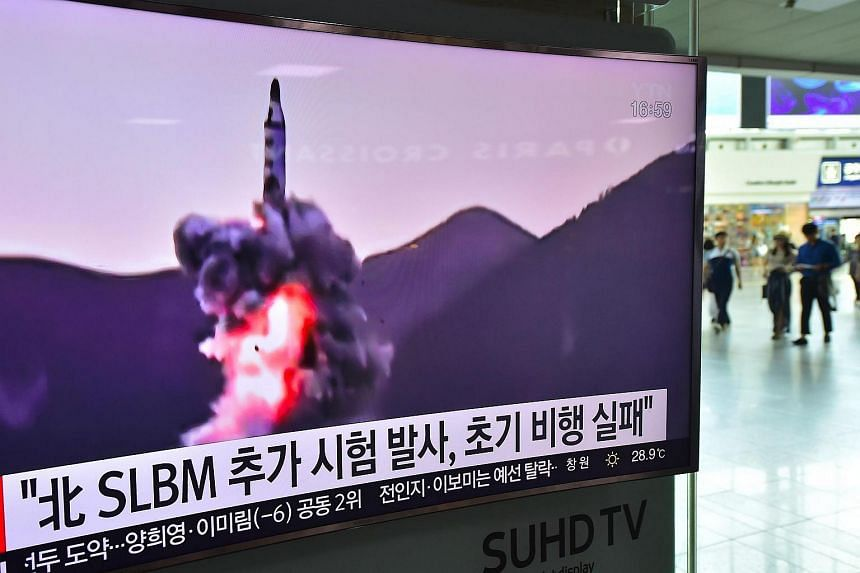 People walk past a television screen at a railway station in Seoul showing file footage of a North Korean missile launch.