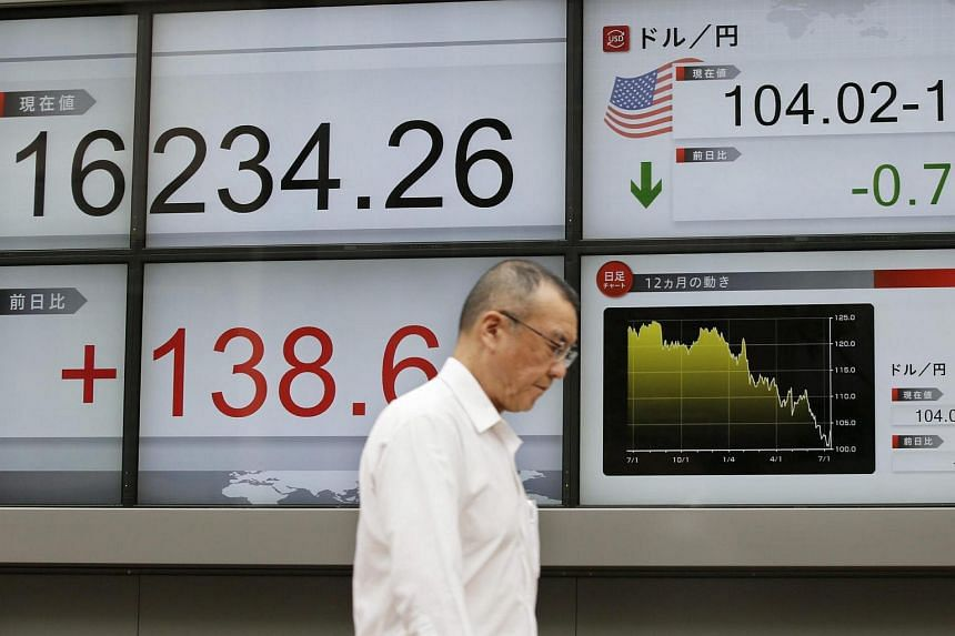 A businessman walks past a display showing Tokyo's Nikkei stock average and exchange rate between the US dollar and the Japanese yen during the morning trade session in Tokyo, Japan, July 13.