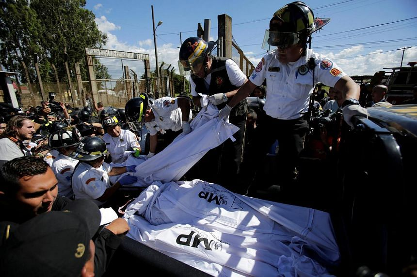Firefighters remove bodies from the Pavon prison following a riot that killed former army captain Byron Lima, convicted for the killing of Bishop Gerardi, in Guatemala City, July 18.