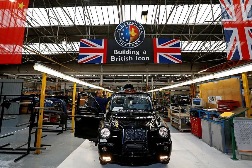 A worker checks a TX4 at the end of the production line at the London Taxi Company in Coventry, central England, in September 2013.
