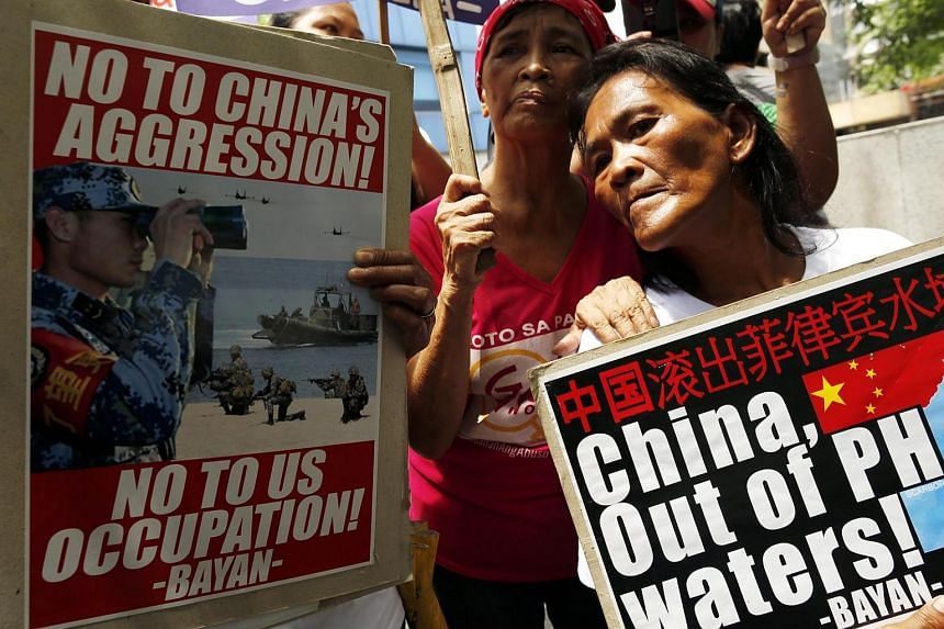 Filipino protestors hold placards as they protest China's territorial claims over the disputed Spratlys group of islands outside the Chinese consular office in Makati city, south of Manila, Philippines, July 12.