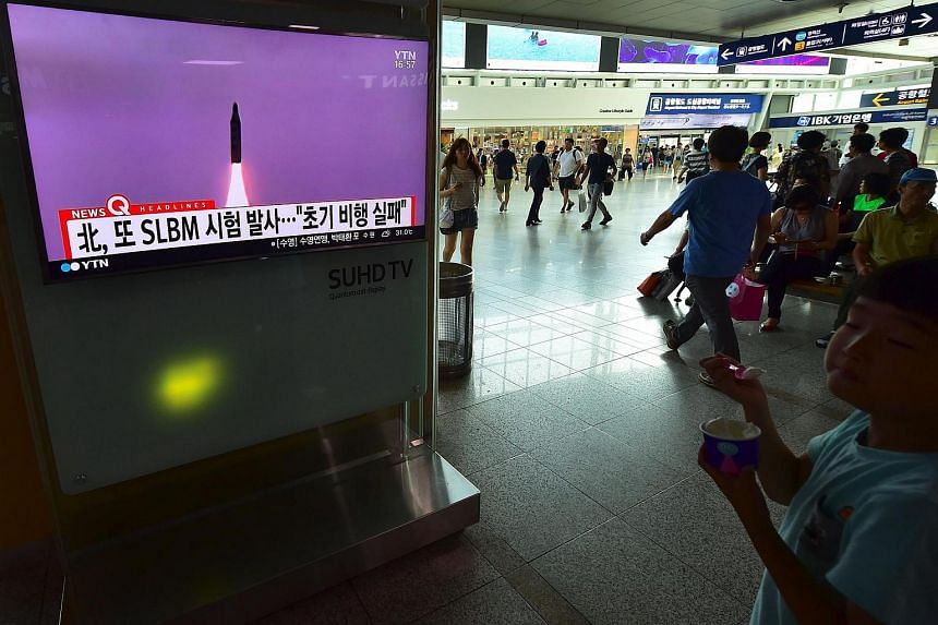 People walk past a television screen at a railway station in Seoul on July 9 showing file footage of a North Korean missile launch.