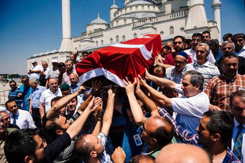 People carry the coffin of coup attempt victim Sehidmiz Murat Inci during his funeral ceremony, at Kocatepe Mosque in Ankara on July 18, 2016.