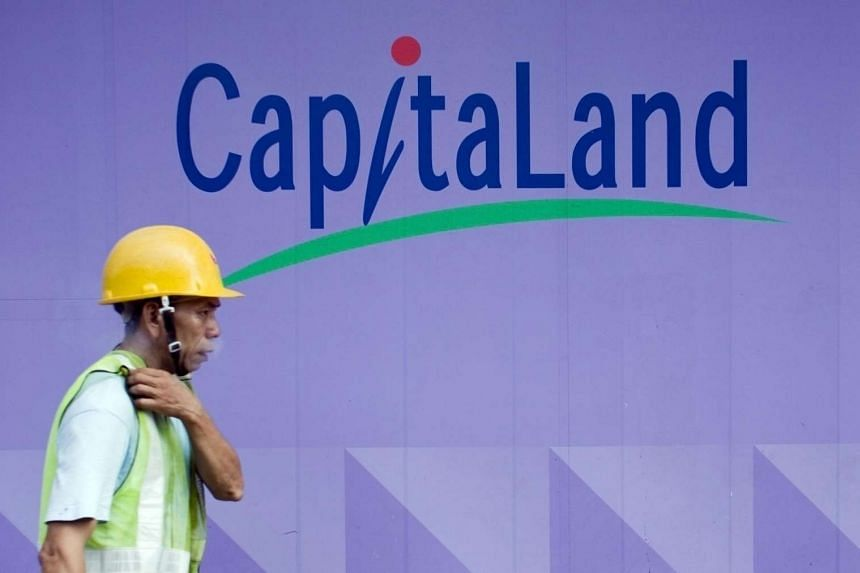 A labourer walks in front of a Capitaland logo at a construction site in Singapore, on Oct 31, 2008.