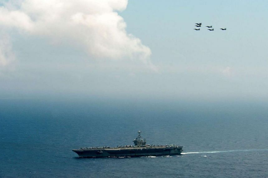 US Navy fighters fly in formation over the aircraft carrier John C. Stennis as it sails in the Philippine Sea, on June 18, 2016.