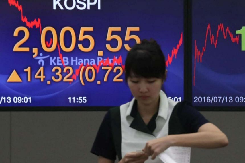 0A Korea Exchange worker stands in front of an electronic board showing the benchmark Korea Composite Stock Price on July 13.