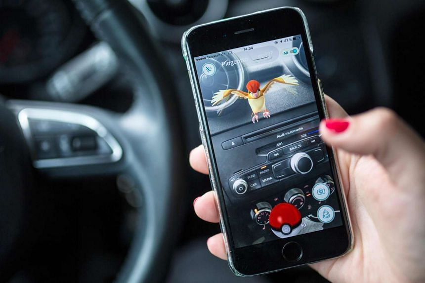 A woman plays the Pokemon Go mobile game on her smart phone in a car on July 13, 2016.