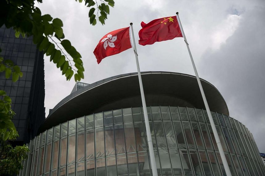 A Chinese national flag (right) and a Hong Kong national flag fly outside the Legislative Council complex in Hong Kong on July 15, 2016.