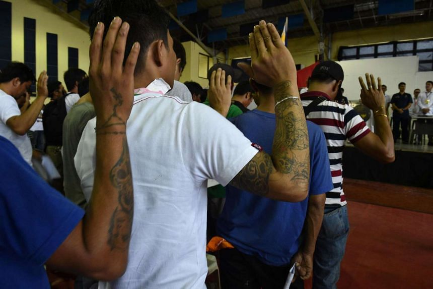 People who have turned themselves in take an oath before local authorities, led by Mayor Thony Halili (back facing camera) during a mass surrender of some 1,000 alleged drug users and pushers in the town of Tanauan, 60 kilometres south of Manila on J