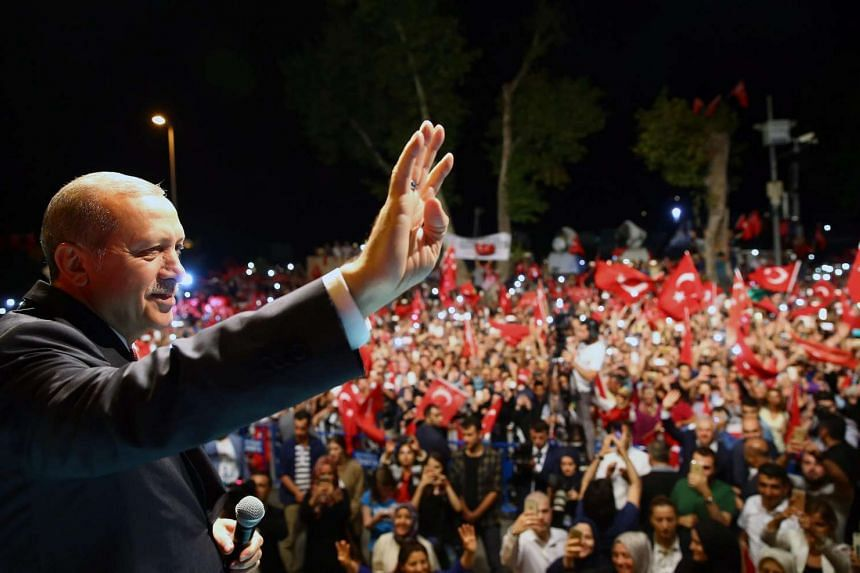 A handout picture shows Turkish President Recep Tayyip Erdogan waving during his rally in Istanbul, Turkey, at midnight on July 18.