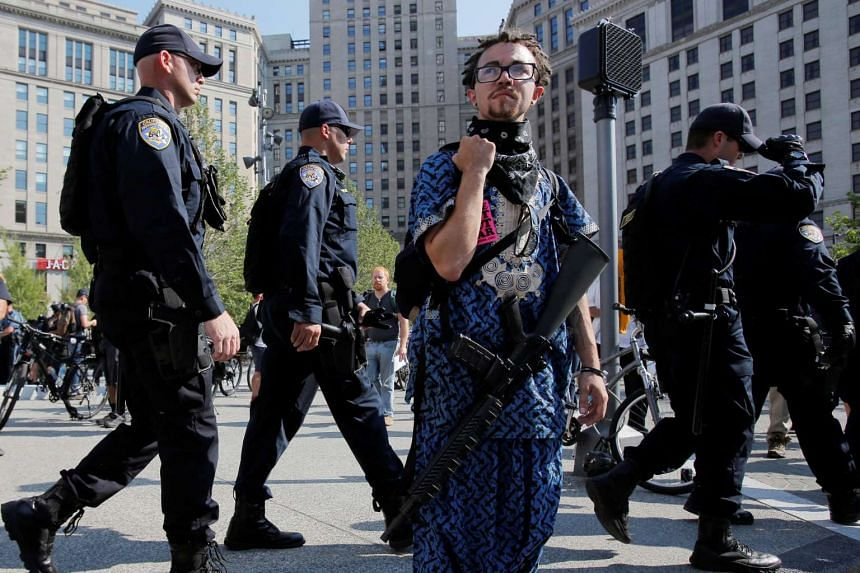 Jaimes Campbell, an advocate for open carry, stands with a gun as police walk by in Cleveland Public Square outside the Republican National Convention on July 19, 2016.