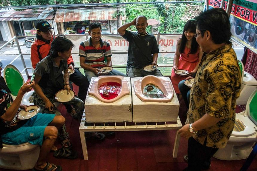 """Customers enjoying a meal at the toilet-themed """"Jamban Cafe"""", where they sit on toilet bowls and food is served out of squat toilets, in Semarang, Java island."""