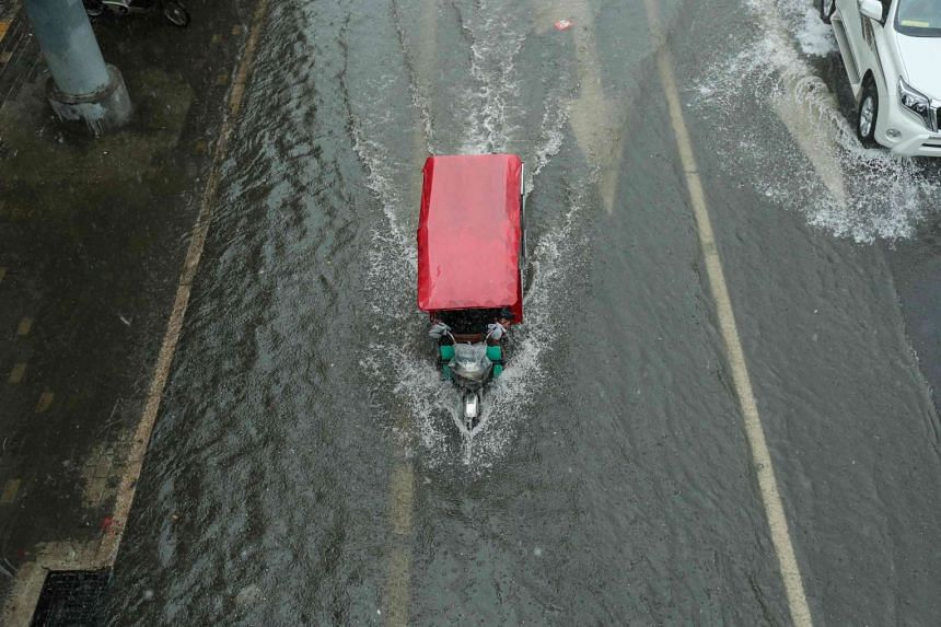 A tricycle makes its way along a flooded street in Beijing on July 20, 2016.