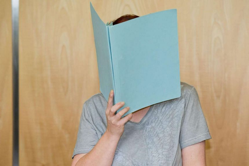 Defendant Andrea G hiding her face as she arrives for the opening of her trial at the district court of Coburg, central Germany on July 12, 2016.
