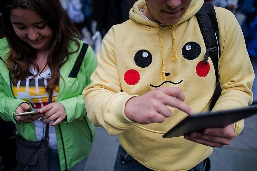 Gamers absorbed in Pokemon Go in the Austrian capital Vienna. The free app uses smartphone satellite location, graphics and camera capabilities to overlay cartoon monsters on real world settings, challenging players to capture and train the creatures