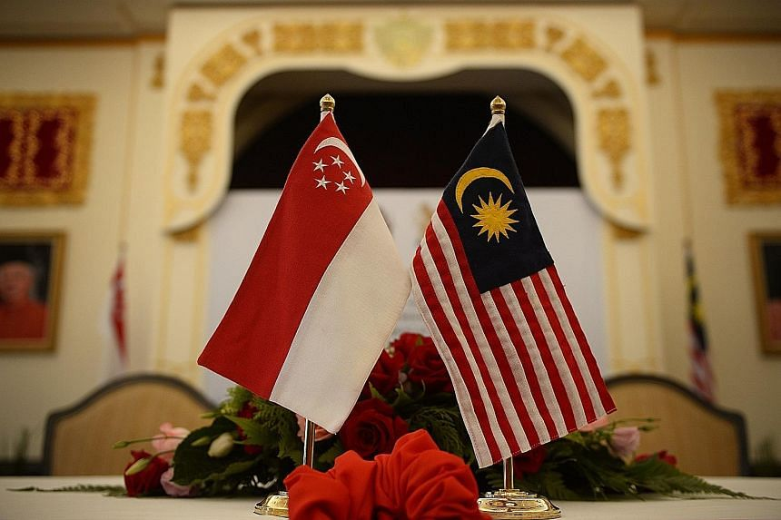 The national flags of Singapore and Malaysia displayed for the signing of the high-speed rail memorandum of understanding at the Malaysian Prime Minister's official residence in Putrajaya yesterday.