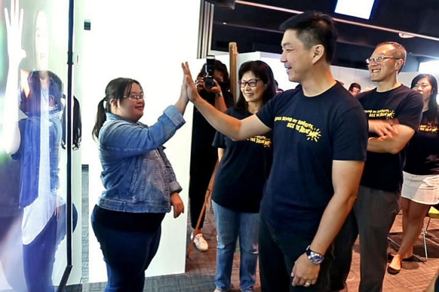 Minister for Social and Family Development Tan Chuan-Jin (second from right) exchanging high fives with Ms Chen Wanyi, who has Down syndrome, at an event on June 2.