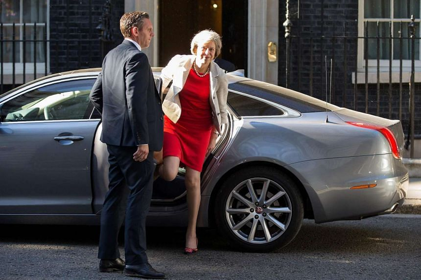 British Prime Minister Theresa May (right) gets out of her car as she arrives at 10 Downing Street in central London on July 18.