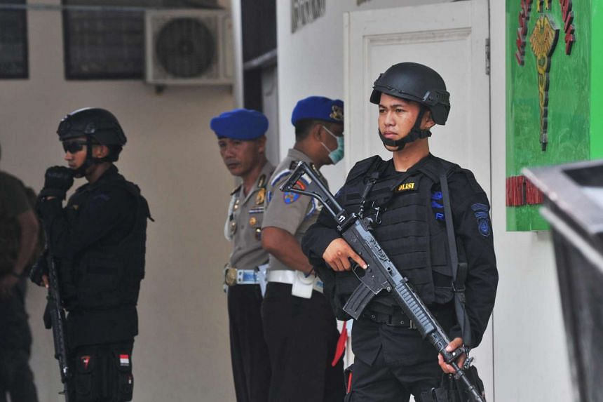 Indonesian security forces stand guard at the hospital where a body believed to be that of the country's most-wanted militant, Santoso, who was killed in a clash with security forces, is lying in Palu, Central Sulawesi, Indonesia on July 19.