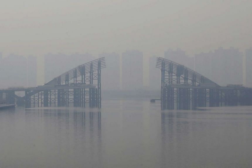 Buildings are seen through smog behind an unfinished bridge near the Yujiapu financial centre, in Tianjin, China.