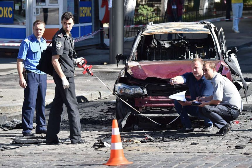 Ukrainian police officers and security services experts examine the charred car of journalist Pavel Sheremet, after he was killed in a car bomb in Kiev on July 20, 2016.