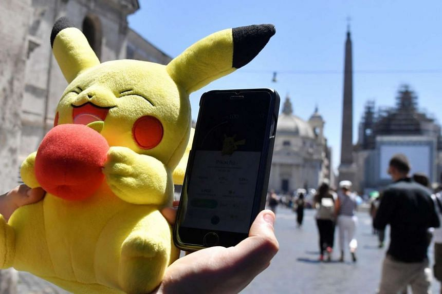 A gamer holds a Pokemon mascot and his mobile phone as he plays Pokemon Go in Rome on July 19.