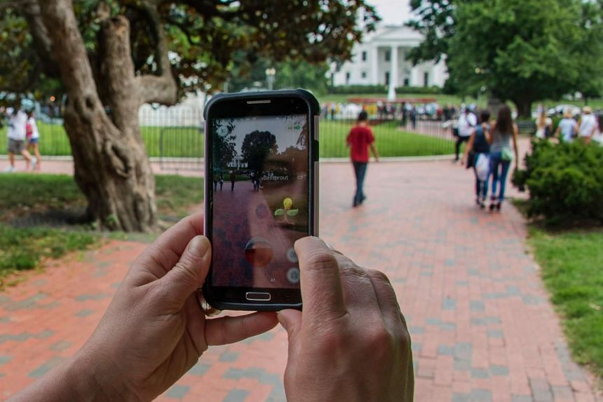 A woman holds up her cellphone as she plays the Pokemon Go game in Lafayette Park in front of the White House.