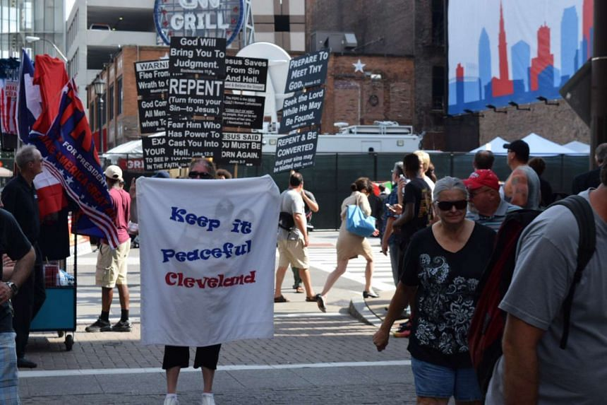 A woman marches for peace through Cleveland's East 4th street cafe district near The Q convention site.