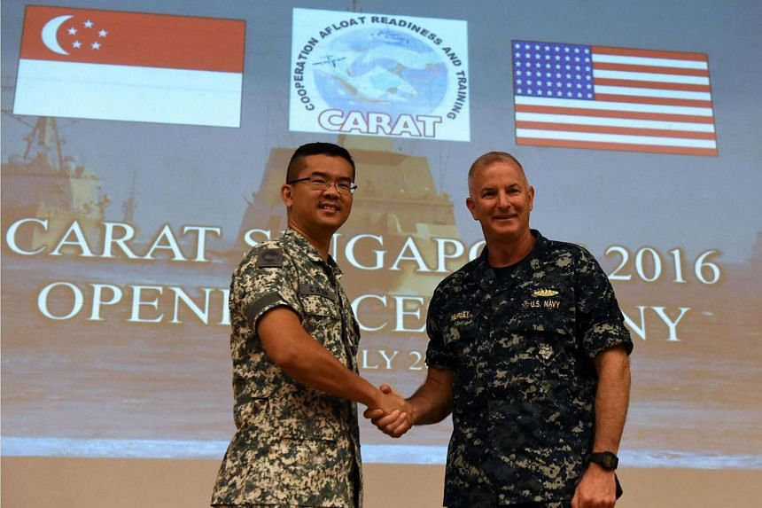 US Navy Rear Admiral Brian Hurley (right), shakes hands with  RSN Fleet Commander Rear Admiral Lew Chuen Hong during the opening ceremony for the Cooperation Afloat Readiness and Training (CARAT) bilateral exercise in Singapore on July 19.
