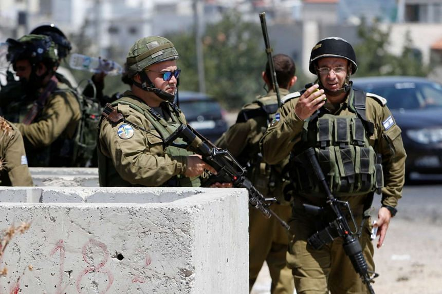 Israeli soldiers at scene of a stabbing attack near the West Bank city of  Hebron on July 18, 2016.
