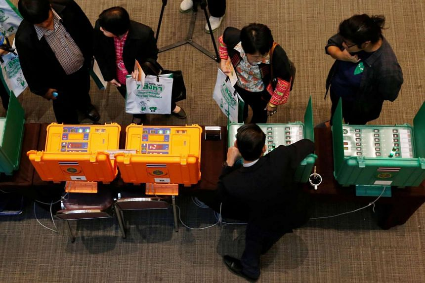 People take a look at Thailand Election Commission's voting machines during an event to kick off the distribution of five million copies of a controversial military-written draft constitution, ahead of the referendum in Bangkok, Thailand