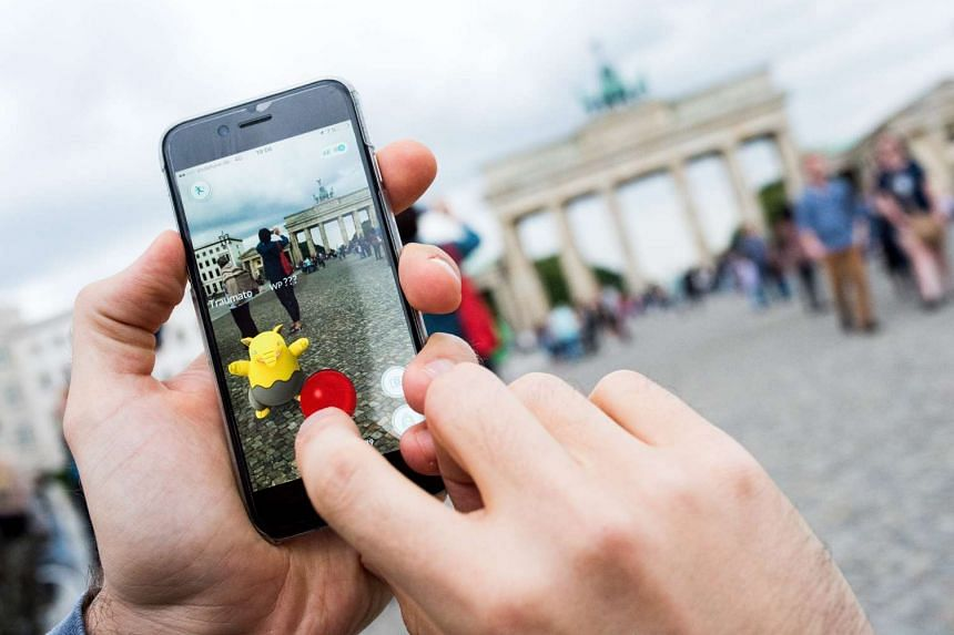 """A man tries to catch a Pokemon called """"Drowzee"""" with a pokeball using the Pokemon Go augmented reality app in Berlin, Germany, July 13,  2016."""