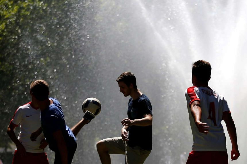 Tourists play soccer near a fountain on a hot summer day in Brussels, Belgium on July 19.
