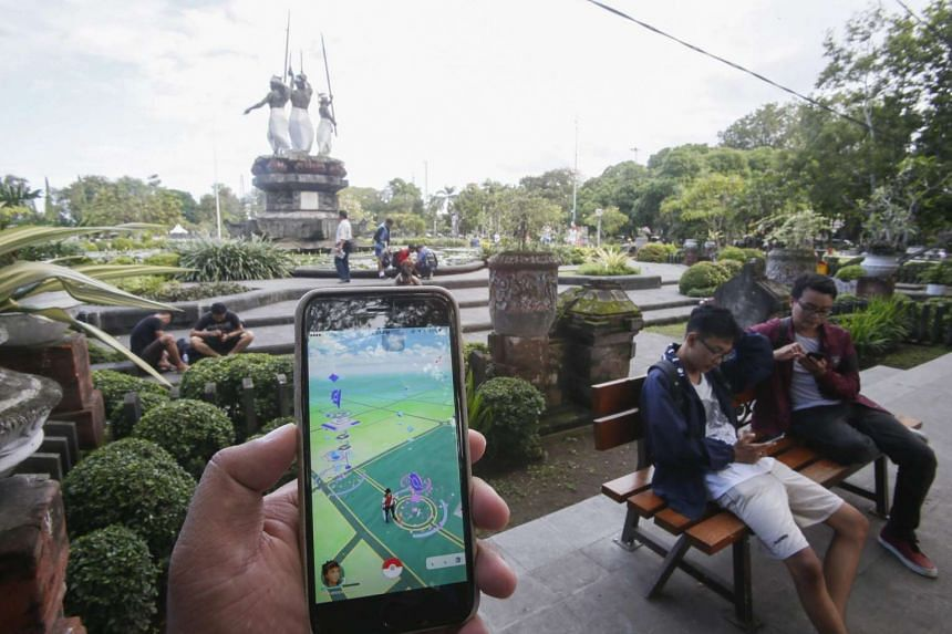A person plays with Pokemon Go on his mobile phone at a park in Denpasar, Bali, Indonesia, on July 20, 2016.