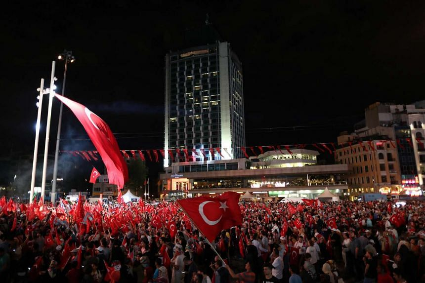 Supporters of Turkish President Recep Tayyip Erdogan shout slogans and hold flags during a demonstration against the July 15 failed coup attempt, at Taksim Square, in Istanbul, Turkey, seen on July 20.