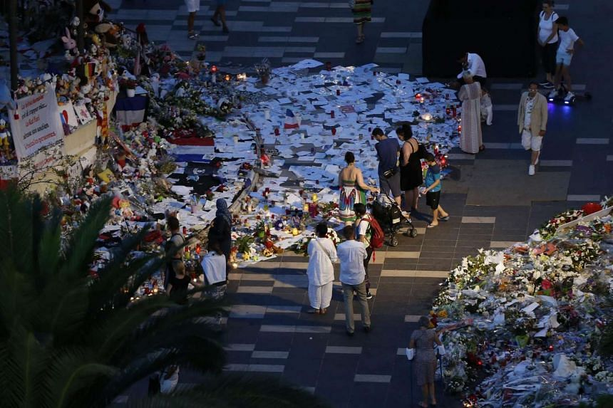 People walk next to floral tributes, notes and candles placed in the road for victims of the deadly Bastille Day attack, on July 20, 2016, in Nice, southern France.