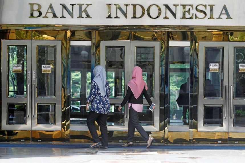 People walk to an entrance at Indonesia's central bank Bank Indonesia in Jakarta, on July 21, 2016.