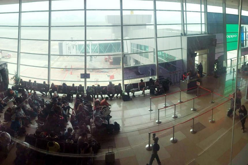 Passengers at Kuching International Airport waiting out their flight delay on July 21, 2016.