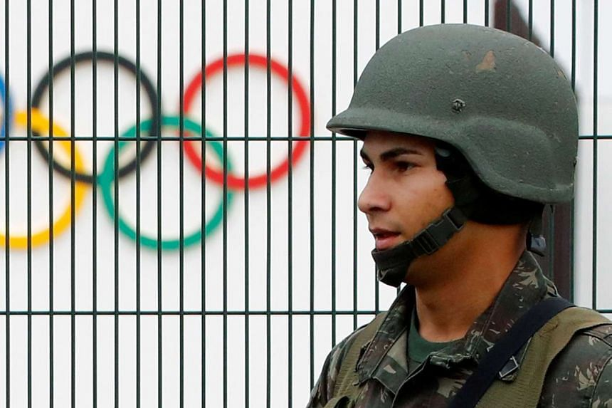 A Brazilian military police soldier patrols at the security fence outside the 2016 Rio Olympics Park on July 21, 2016.