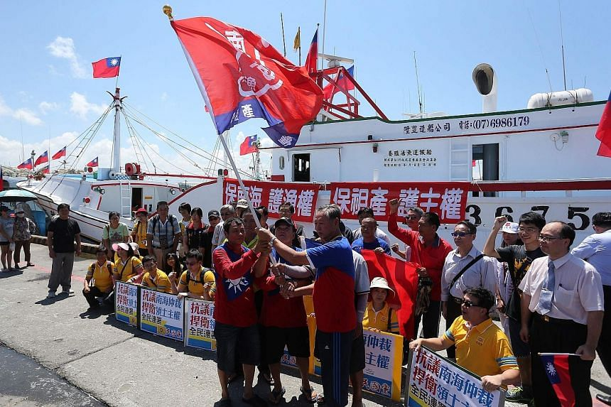 """Taiwanese fishermen holding flags and signs reading """"Protect fishing rights, safeguard sovereignty"""" before heading to Taiping in the Spratlys archipelago. Lawmakers from the ruling DPP and opposition KMT also flew there to visit facilities that show"""