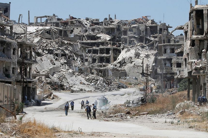 Workers collecting rubble of damaged buildings to be recycled and reused for reconstruction, under the supervision of the United Nations Development Programme in the government- controlled district of Wadi al-Sayeh in Homs, Syria, on Tuesday.